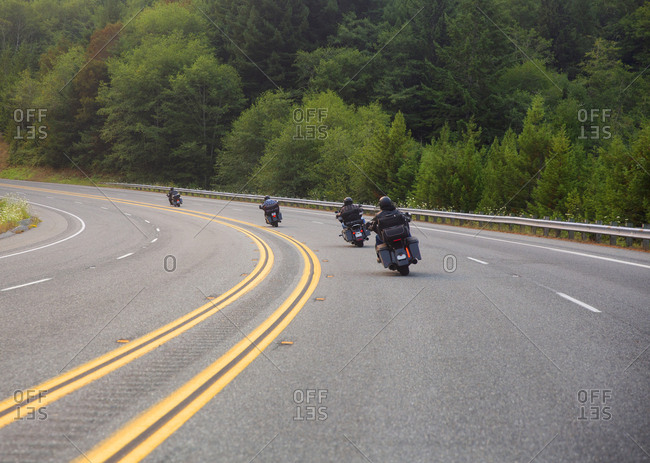 Motorcycles driving south on Highway 101 near a redwood forest, California, USA