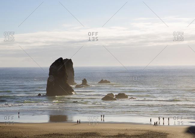 Tourists enjoying the view at Cannon beach, Oregon, USA