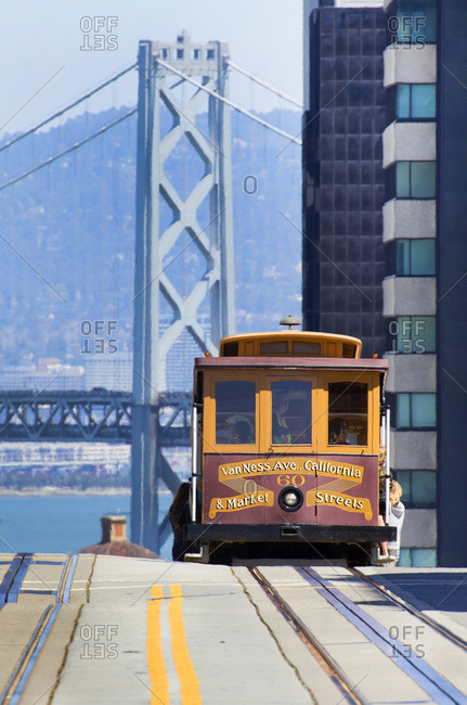 San Francisco, California, USA - August 9, 2015: View of a cable car and Oakland bay bridge background
