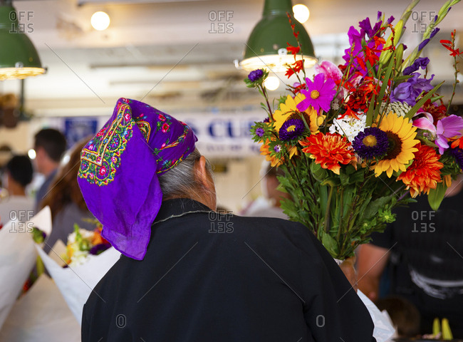 Seattle, Washington, USA - August 3, 2015: Lady flower seller preparing bouquets of flowers at the Pike street market