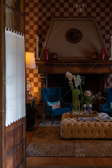Franciacorta, Italy - September 15, 2019: Two armchairs and large ottoman beside a fireplace
