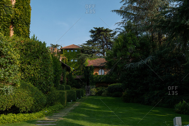 Franciacorta, Italy - September 15, 2019: Exterior of a large home surrounded by lush green foliage