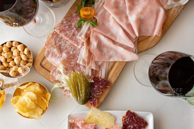 Overhead view of a meat board appetizer served with wine