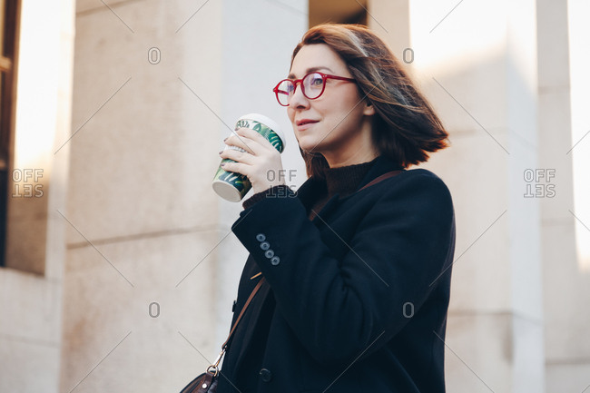 Young business woman holding and drinking from reusable coffee bamboo cup in the city. Concept of reusing and recycling.