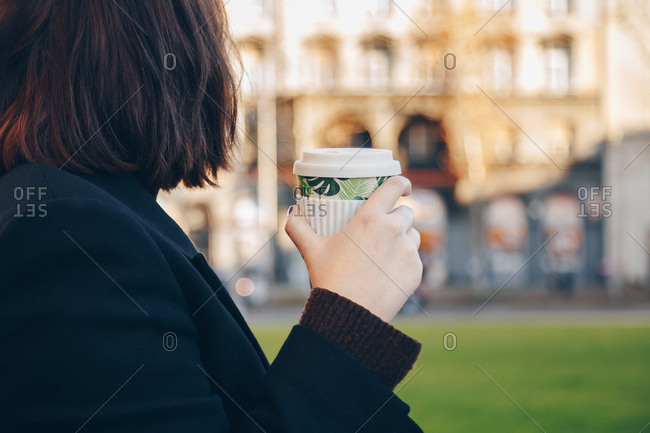 Detail shot, young business woman holding reusable coffee bamboo cup in the city. Concept of reusing and recycling.