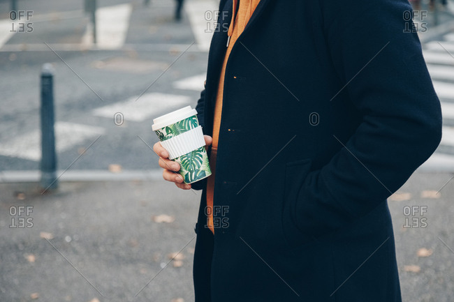 Detail shot, man holding reusable coffee bamboo cup in the city. Concept of reusing and recycling.