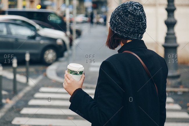 Young business woman posing holding reusable coffee bamboo cup walking in the city. Concept of reusing and recycling.