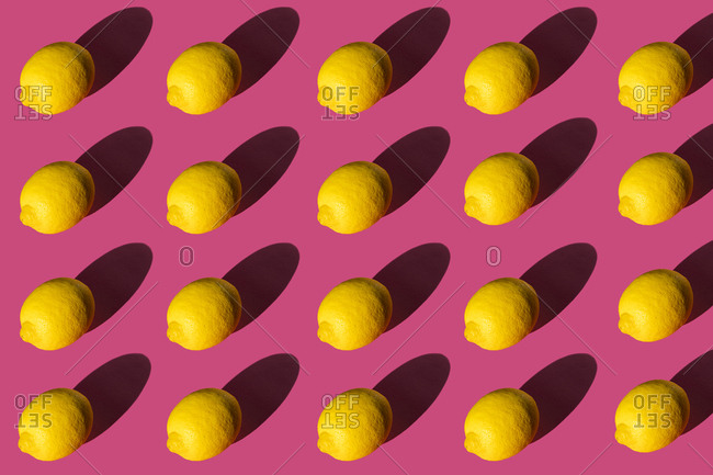 Composition of lemons with hard shadows on a pink background