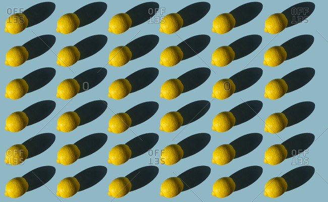 Composition of lemons with hard shadows on a blue background