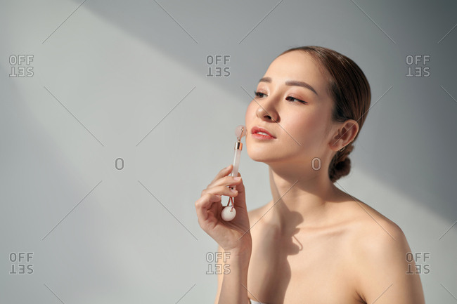 Woman using a rose quartz face roller on her flawless skin
