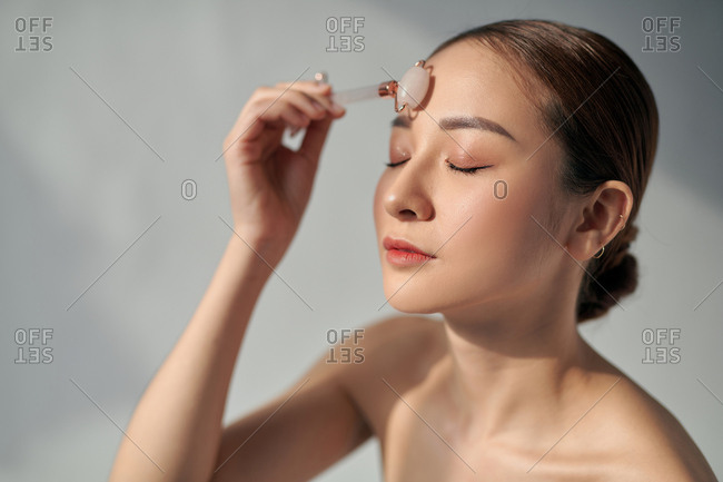 Asian woman using a rose quartz face roller on her flawless skin