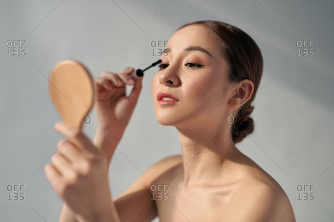 Beautiful Asian woman putting on mascara