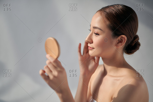 Beautiful young woman looking at herself in a small mirror