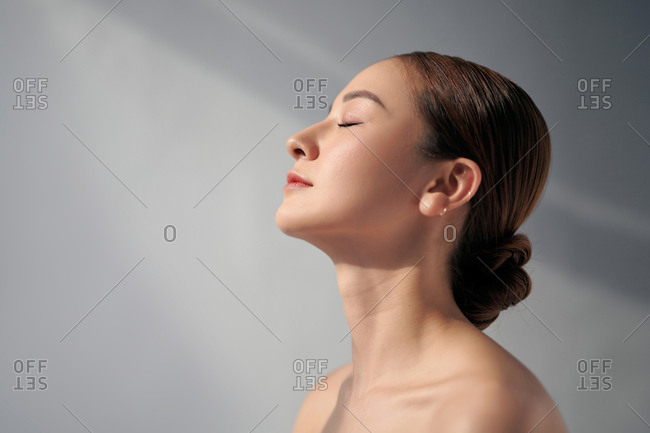 Profile of a beautiful woman with bare shoulders and her closed eyes