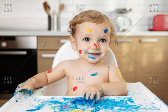 Baby sitting in high chair with finger paint on face and body