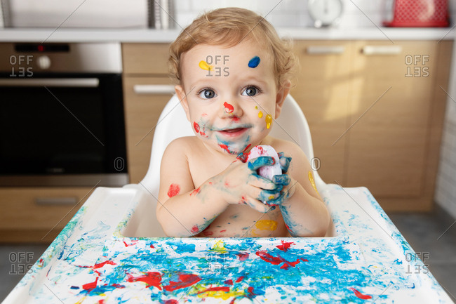Cute baby in high chair with finger paint on face and body