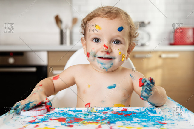 Happy baby in high chair with finger paint on face and body