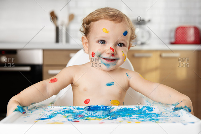 Cute smiling baby in high chair with finger paint on face and body