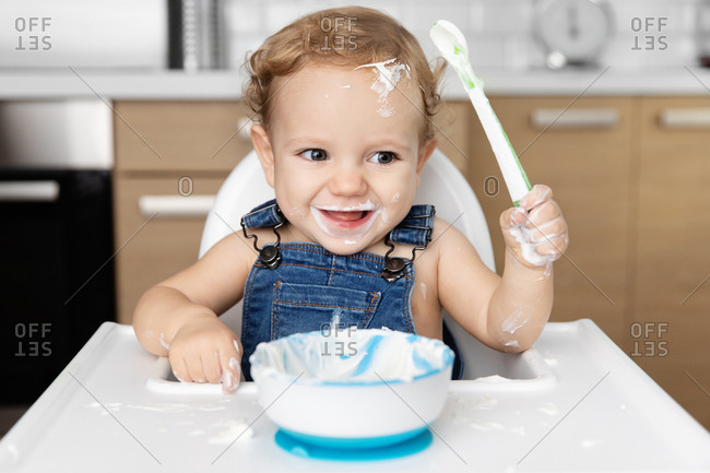 Happy baby with messy face eating yogurt with spoon