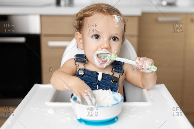 Cute baby with messy face eating yogurt with spoon in high chair