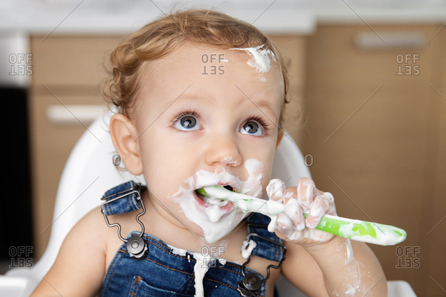 Close up portrait of baby with messy face eating yogurt with spoon