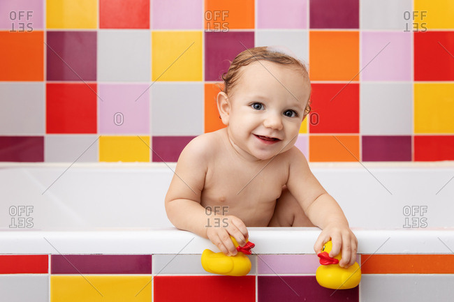 Smiling baby in bathtub holding rubber ducks