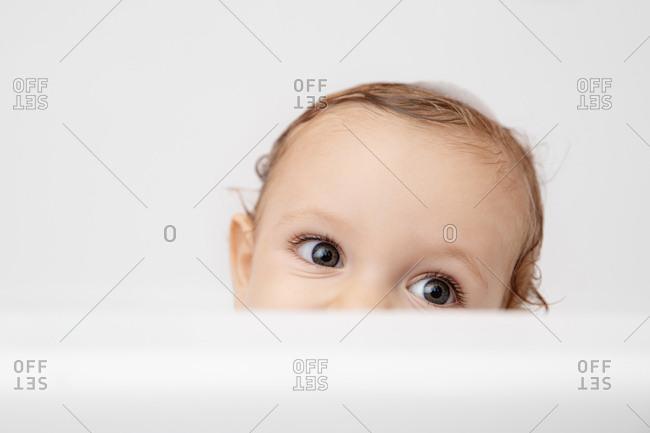 Eyes of baby peeking over white bathtub