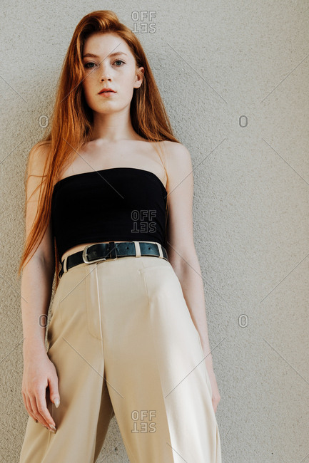 The fashion portrait of young redhead ginger woman in stylish look in urban background
