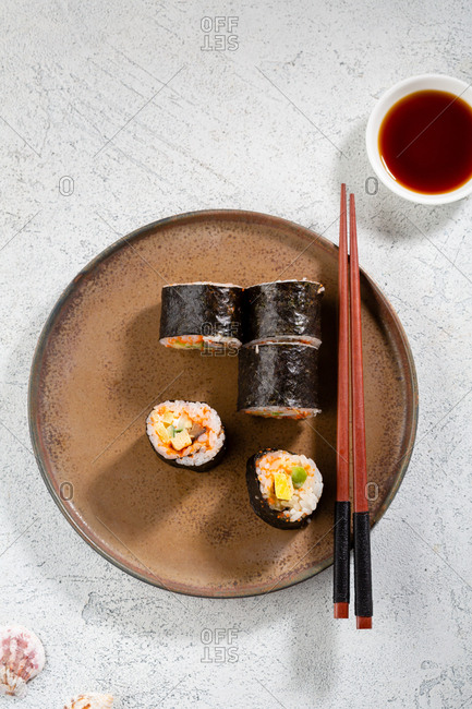 Sushi roll on a plate with chopsticks