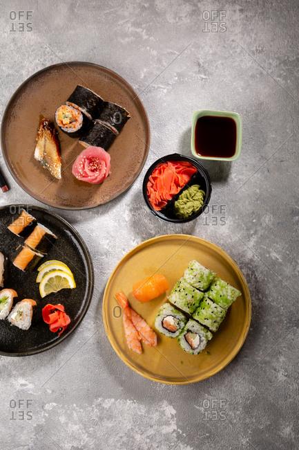 Various sushi rolls and nigiri on ceramic plates