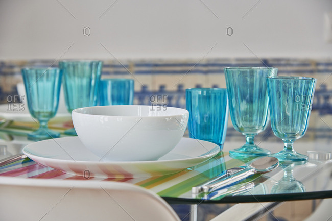 White dishes and blue glasses on a glass table, Lisbon, Portugal