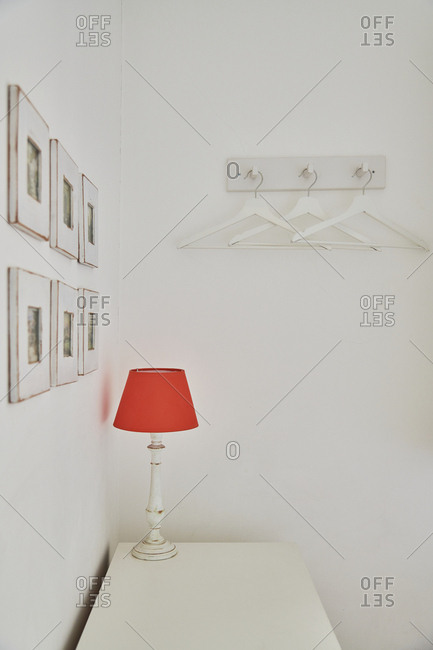 Lamp with red lampshade on a white dresser in a white room