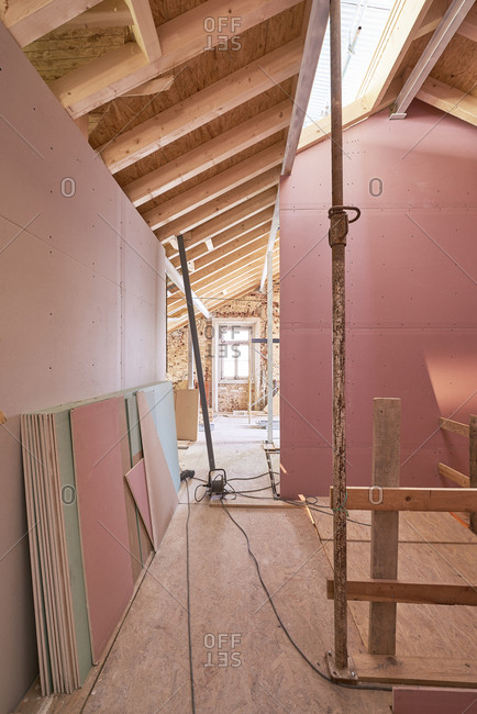 A construction site with pink drywall and skylight