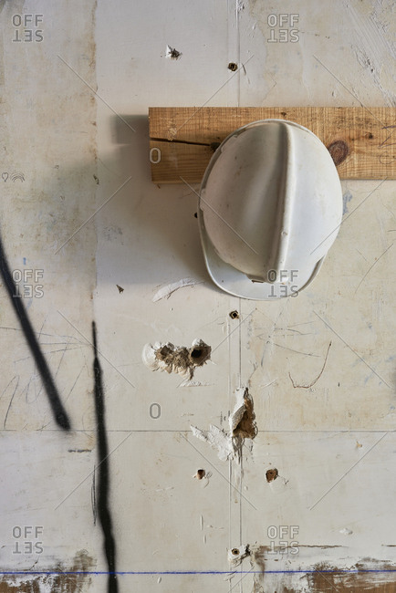 Hard hat hanging on wall at construction site