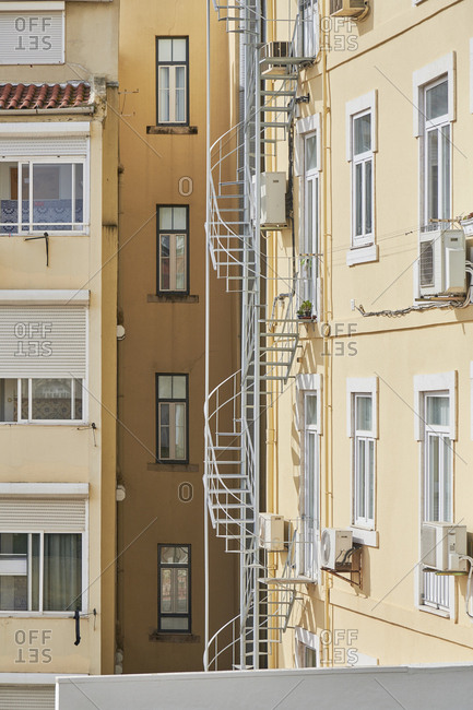 Yellow apartment building with fire escape in the city of Lisbon, Portugal