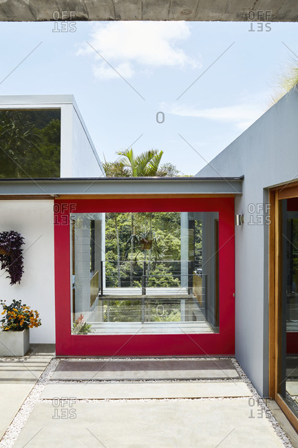 Costa Rica, Central America - July 30, 2019: Red trim around large window on exterior of modern home