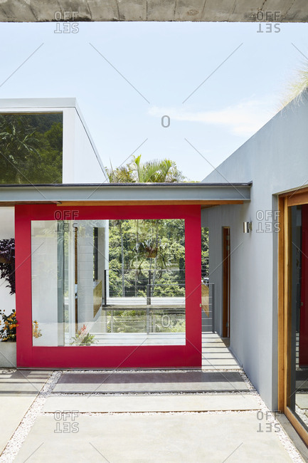 Costa Rica, Central America - July 30, 2019: Red trim around large sliding glass door on exterior of modern home