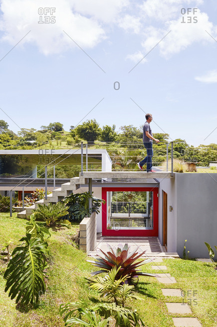 Costa Rica, Central America - July 30, 2019: Man walking above red trimmed door on a modern home