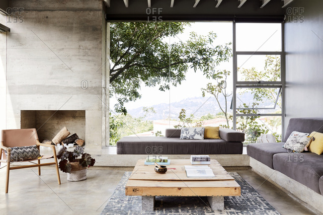 Costa Rica, Central America - July 30, 2019: Large windows by stone fireplace in a modern home