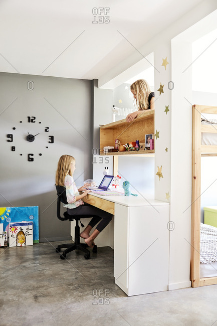 Costa Rica, Central America - July 31, 2019: Two girls in their bedroom climbing on bunk bed and doing homework at desk