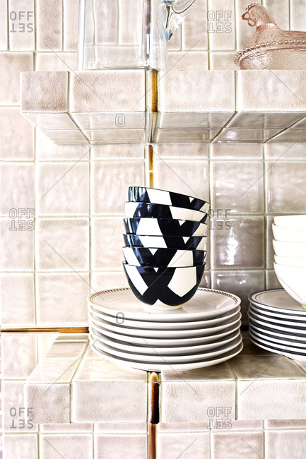 Dishes stacked in a kitchen with tile walls and shelves of home in Provo, Utah