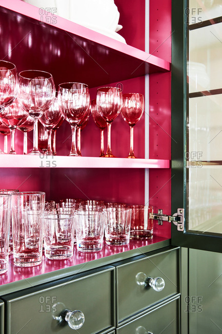 Glassware neatly arranged in a green and red cabinet in a home in Provo, Utah