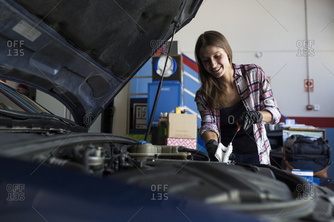 Young casual woman in shirt and gloves working with car in repair service checking engine oil level