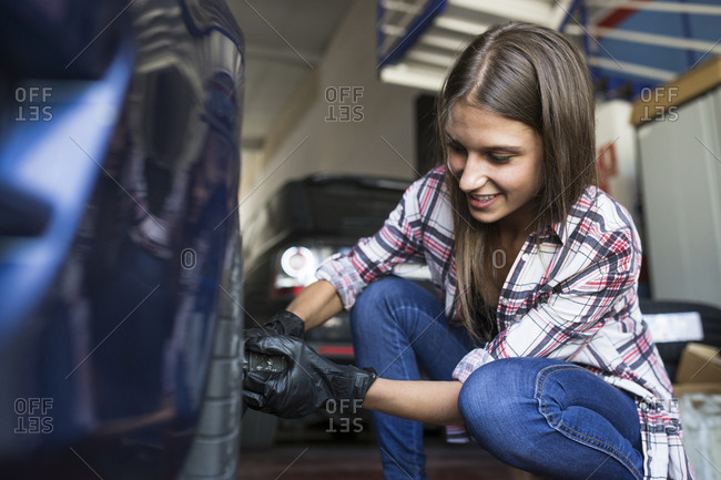 Young woman wearing gloves and screwing wheel of car working in repair shop