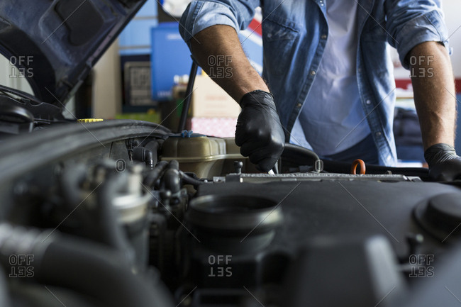 Man in shirt and gloves working in car repair service and fixing car engine