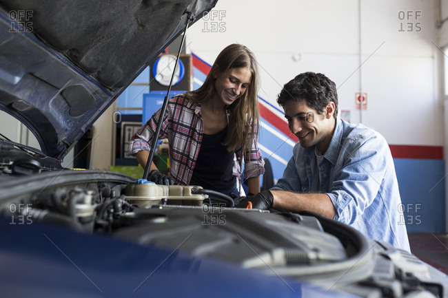 Cheerful man and young woman working together on car repair service and fixing car engine