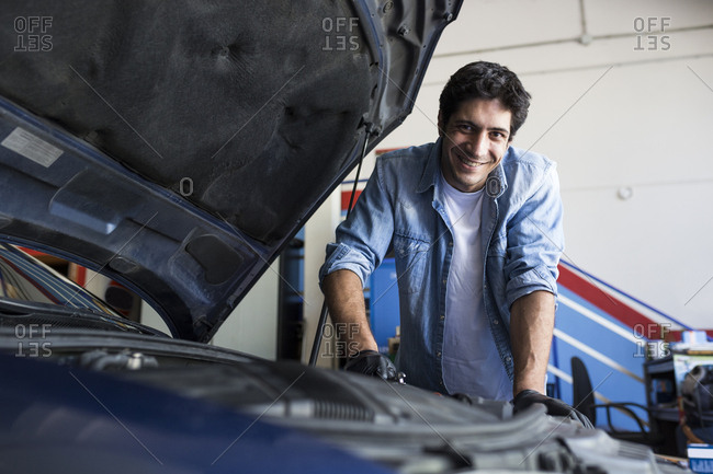 Cheerful man working in car workshop and fixing car engine with tool smiling at camera