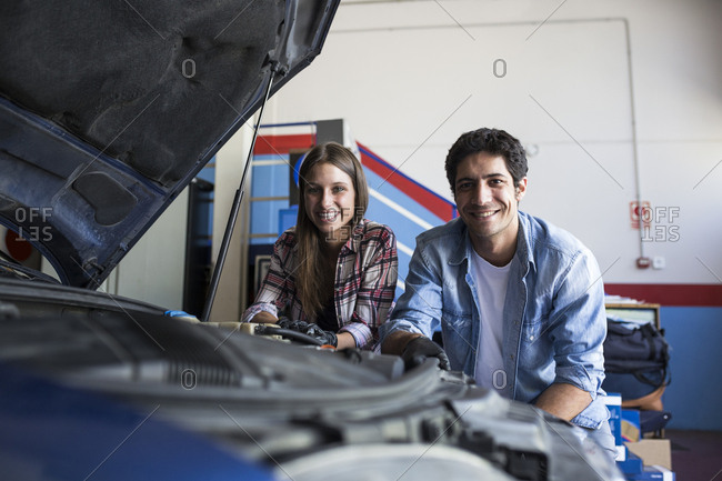 Young woman and man standing near car in service center smiling at camera and working in team
