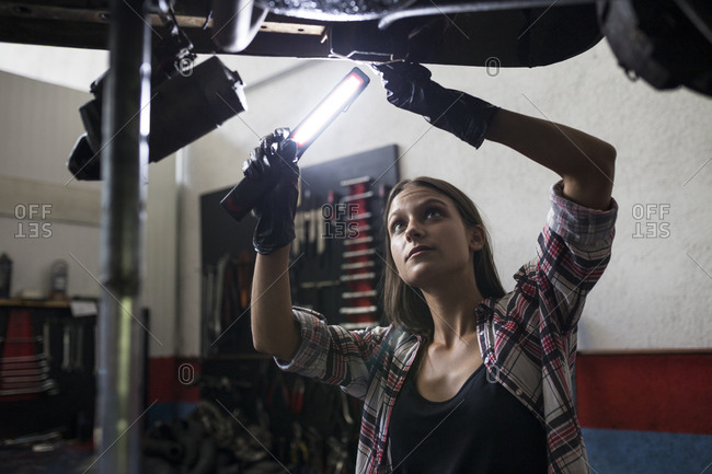 Brunette woman in shirt holding burning lamp and working with car standing under bottom in car repair shop