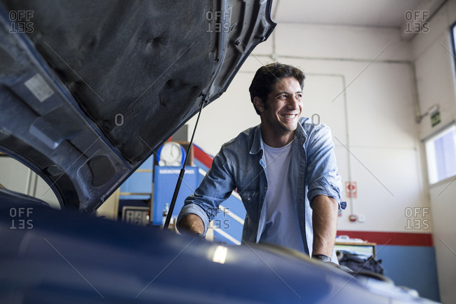 Smiling man working with engine of car in repair service and looking away